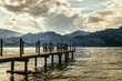 Scenery with wooden dock pier extending over blue lake water and mountains
