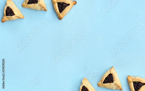 Triangular cookies with poppy seeds ( hamantasch or aman ears ) for jewish holiday of purim celebration on blue paper background with space for text Canvas Print