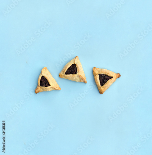 Photo Triangular cookies with poppy seeds ( hamantasch or aman ears ) for jewish holiday of purim celebration on blue paper background with space for text