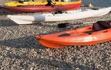 Colourful Kayaks On A Pebbly B...