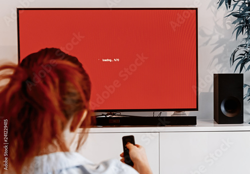 woman sitting in her living room and holding a TV remote control in front of a s Tablou Canvas