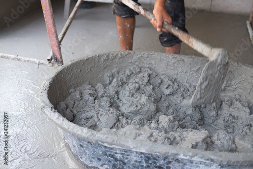Photo  Concrete mixing step of sand cement and water by construction workers