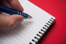 Closeup Of Hand Of Man Writing With Blue Pen On Spirales Note Book On Red Background