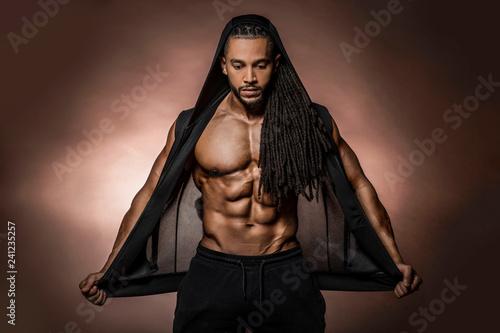Modèle de fitness athlétique noir afro-américain musclé portant un sweat à capuche noir avec six pack abs en studio avec éclairage dramatique sur fond marron – Image de Acheter stock libre de droits et découvrez des images similaires sur Adobe Stock   – abdo