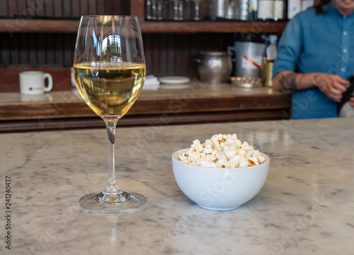 Fotografie, Obraz  Wine glass filled with white wine standing next to a bowl of fresh popcorn with