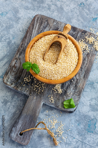Raw organic quinoa seeds in a wooden bowl.