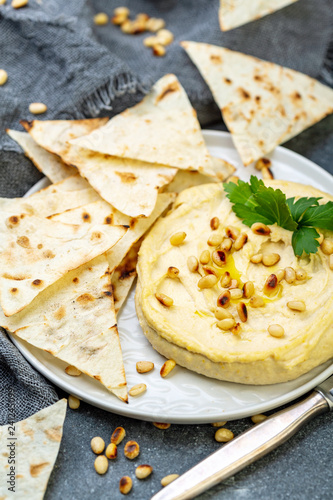 Traditional hummus with pine nuts and pita bread.