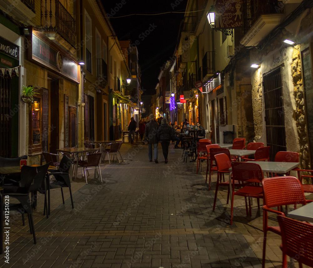 Obraz NIGHT PHOTO OF A STREET BAR AREA WITH PEOPLE fototapeta, plakat