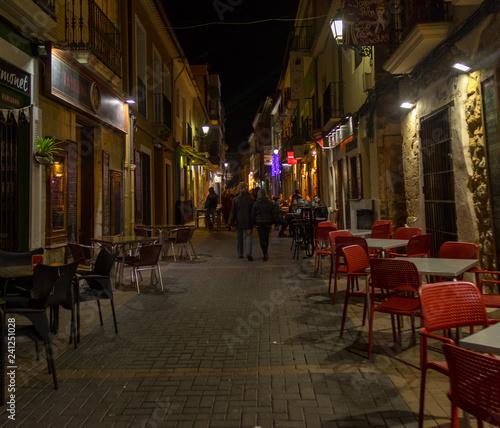Fototapeta NIGHT PHOTO OF A STREET BAR AREA WITH PEOPLE obraz