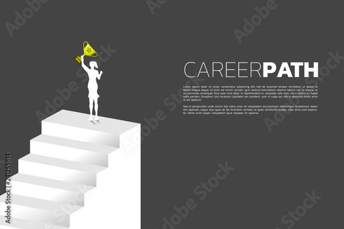 Fotografía  Silhouette of businesswoman with golden trophy on top of stair