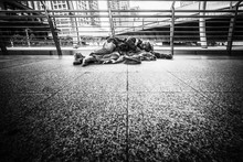 Poor Homeless Beggar Laying And Sleeping On Pathway In Black And White Tone