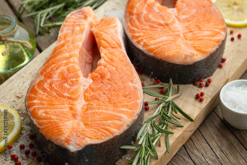 Two raw salmon fish steaks with lemon slices, salt and rosemary on cutting board.
