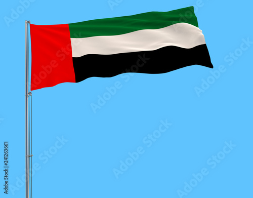 Fotografía  Isolate flag of United Arab Emirates on a flagpole fluttering in the wind on a blue background