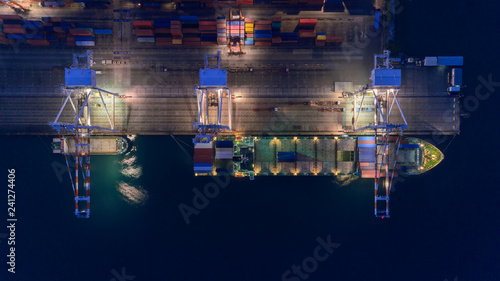 Valokuva  Aerial top view container ship at sea port and working crane bridge loading container for logistics import export, shipping or transportation
