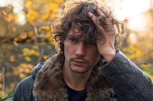 Fotografie, Obraz  ritratto in cui un giovane uomo si tocca i capelli sotto il sole che illumina la