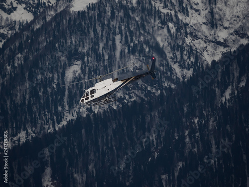White helicopter flies over snowy forest on a cloudy day