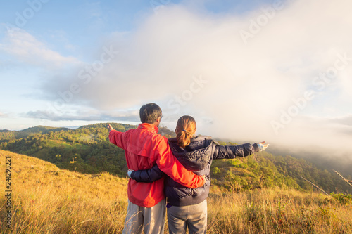 Photo  rear of happy couple love stand on top mountain looking view with mist and cloud at Doi Langka Luang, Chiang Rai province