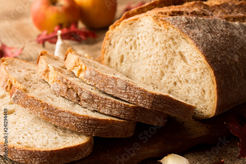 Fototapeta   Pokorojony świeży chleb w kompozycji z jesiennymi liśćmi i czosnkiem. obraz