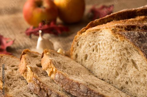 Pokorojony świeży chleb w kompozycji z jesiennymi liśćmi i czosnkiem Canvas-taulu