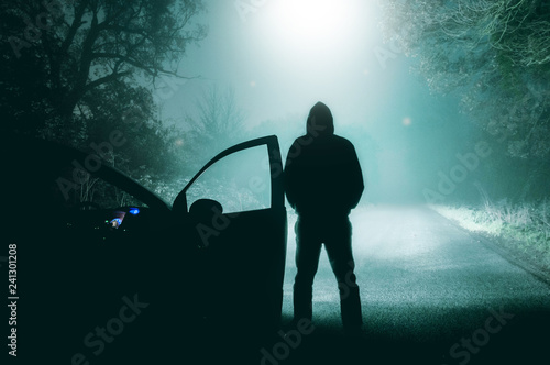 Photo sur Toile UFO A lone, hooded figure standing next to a car looking at an empty misty winter country road silhouetted at night by a UFO.