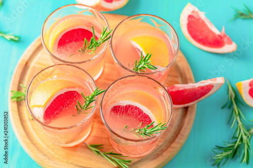 Fotografía  Fresh pink alcoholic cocktail with grapefruit, ice and rosemary