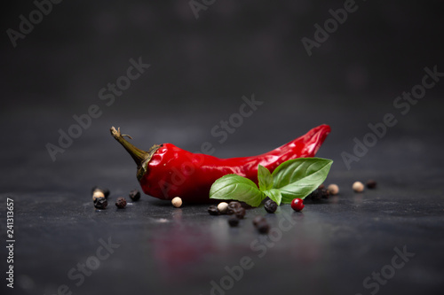 Fotobehang Hot chili peppers chili pepper with basil and peppercorns on a rustic surface