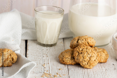 Tuinposter Koekjes Oatmeal cookies with milk on tray on rustic wooden table