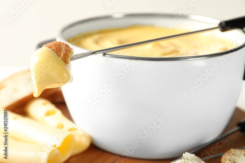 Pot of delicious cheese fondue and fork with bread on table