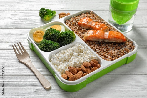 Container with natural healthy lunch and fork on table. High protein food