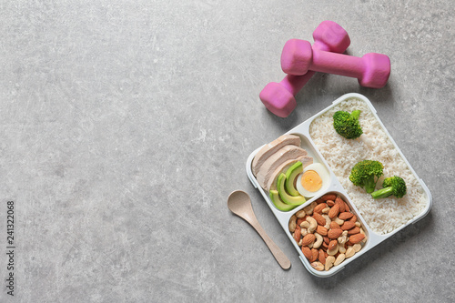 Container with natural healthy lunch, dumbbells and space for text on table, top view. High protein food