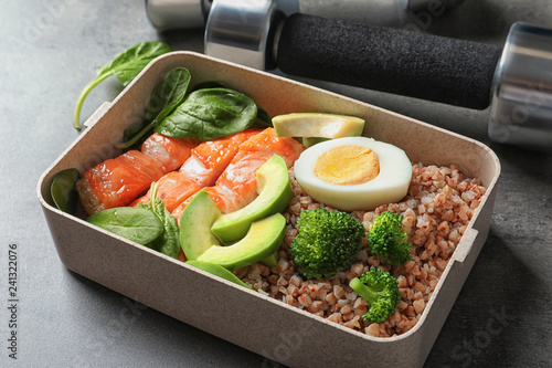 Container with natural healthy lunch on table. High protein food