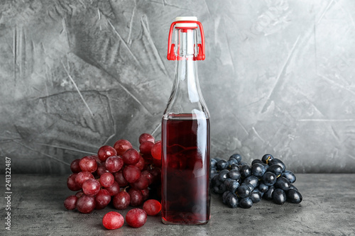 Bottle with wine vinegar and fresh grapes on gray table