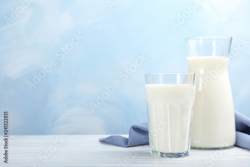 Glass and cruet with fresh milk on table against color background. Space for text
