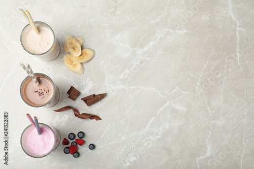 Glasses with different protein shakes and ingredients on grey background, top view. Space for text