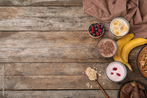 Flat lay composition with protein shakes and ingredients on wooden table. Space for text