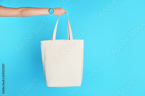 Woman holding eco bag on color background. Mock up for design Canvas Print