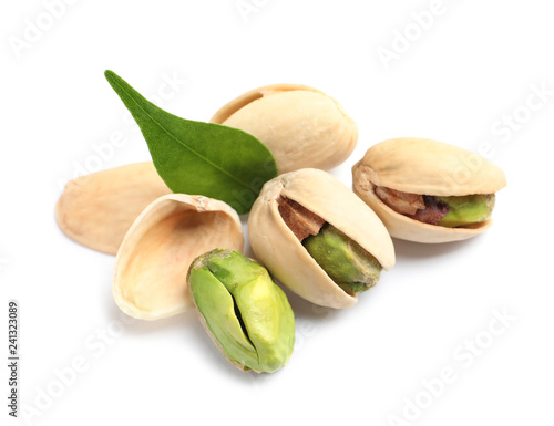 Tasty organic pistachio nuts and leaf on white background, closeup