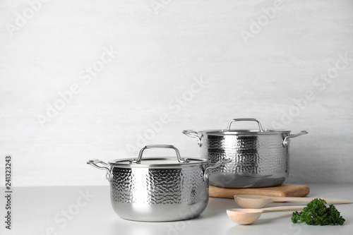 Clean saucepans and spoons on table against light background. Space for text