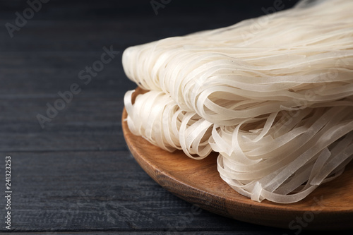 Plate with raw rice noodles on wooden table. Space for text