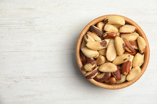 Bowl With Tasty Brazil Nuts And Space For Text On White Wooden Background, Top View