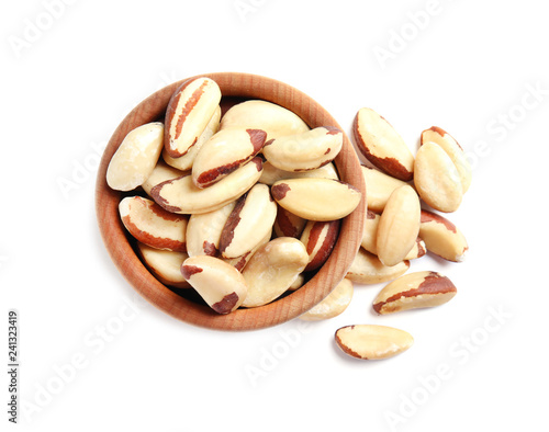 Wooden bowl with Brazil nuts on white background, top view