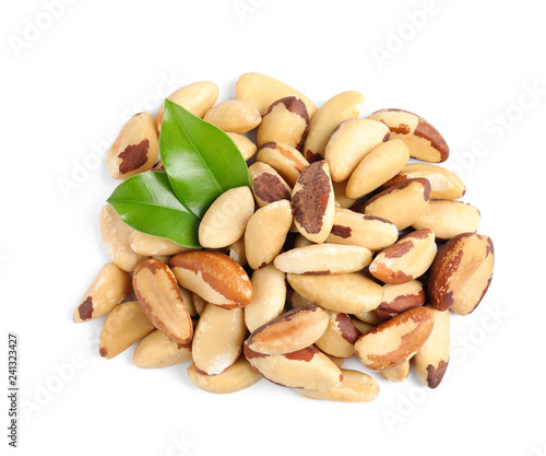 Brazil nuts with green leaves on white background, top view