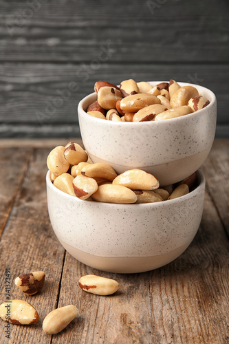 Bowls with tasty Brazil nuts on wooden table