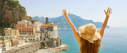 Summer holiday in Italy. Panoramic back view of young woman with straw hat with raised arms looking at Atrani village, Amalfi Coast, Italy.