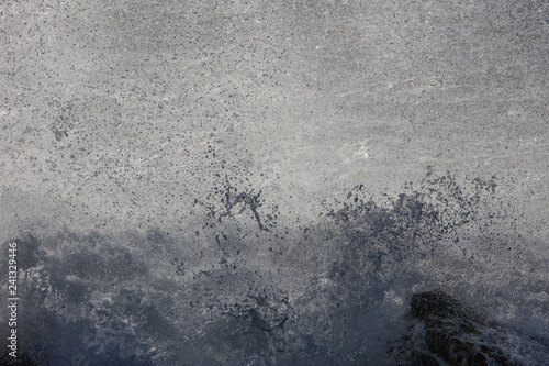 Fotografiet  Spray from Powerful Wave Crashing on Shore