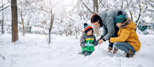 Mother Helping Son Putting On Snow Gloves