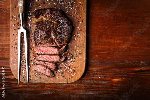 Fotobehang Steakhouse tasty and fresh, very juicy ribbey steak of marbled beef, on a wooden table.