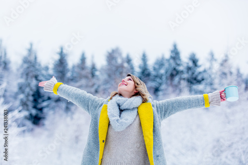 Beautiful girl in coat with cup of hot drink in a snow forest. Christmas of Valentine Day season time