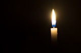 A single candle light glowing on a white candle on black background