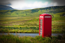 Typical Red English Telephone Box In A Rural Area Near A Road.